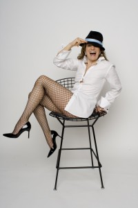 Regena with chair in fishnets, heels and a sassy hat.